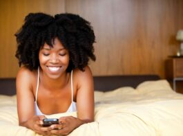 A black woman lying in bed using a cell phone.